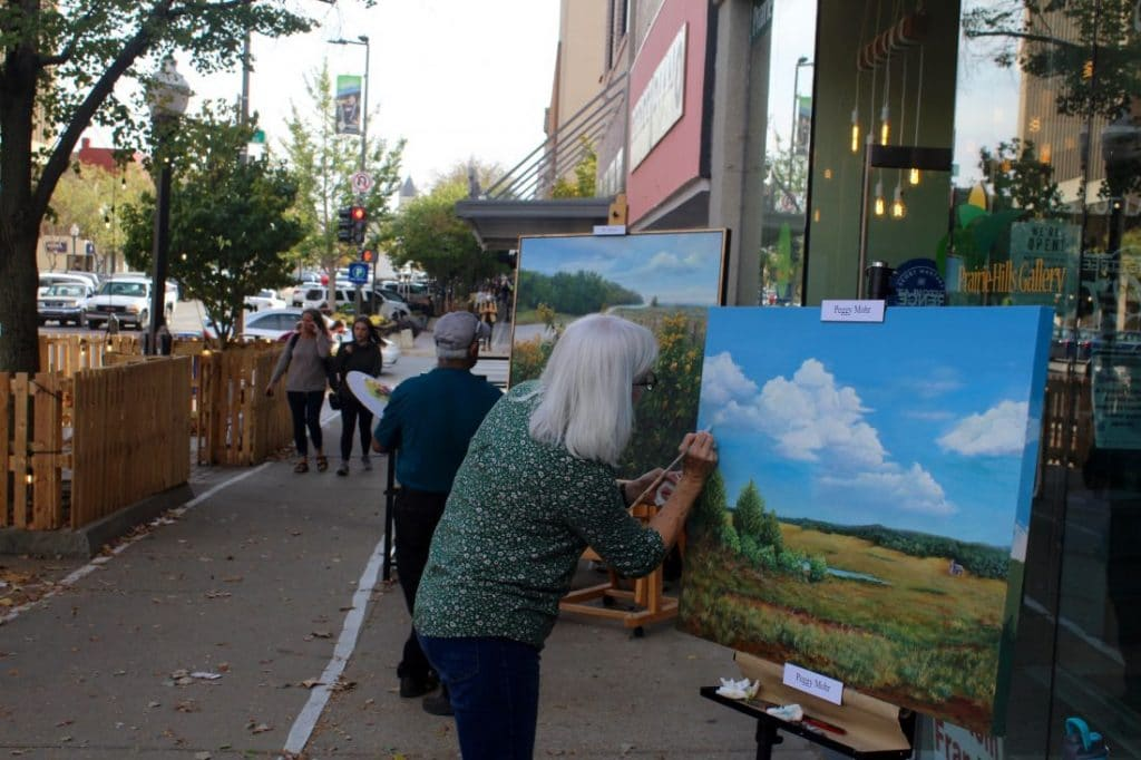 Artitst Painting Outside Prairie Hills Gallery in Lawrence, KS from the Lawrence Journal World